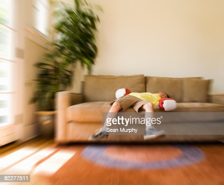 Boy lying on sofa with boxing gloves on : Stock Photo