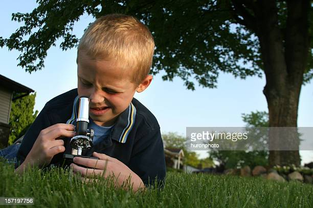 Boy lying on stomach in grass looking into a microscope