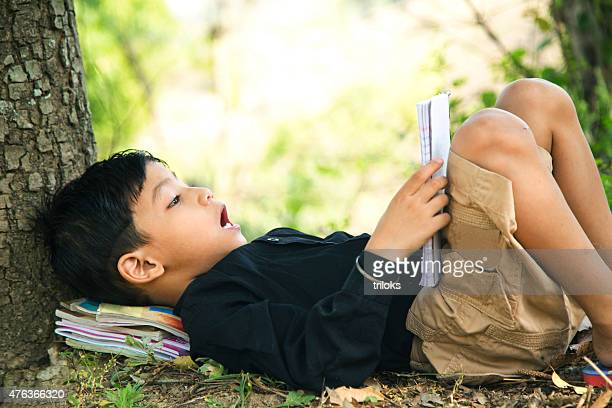 Boy lying under tree and reading book