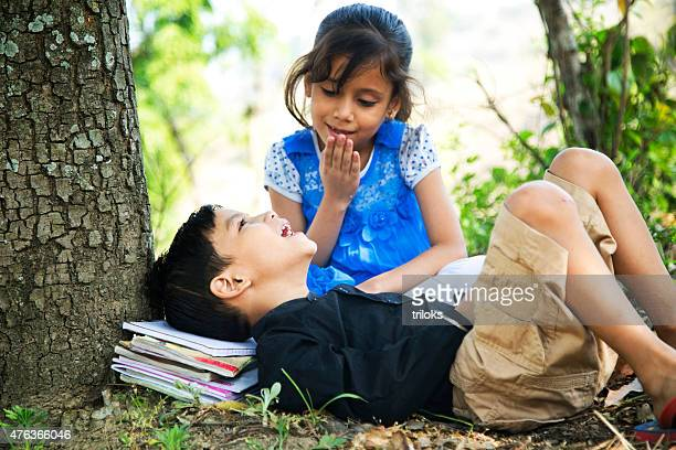 Boy lying under tree with his sister and smiling