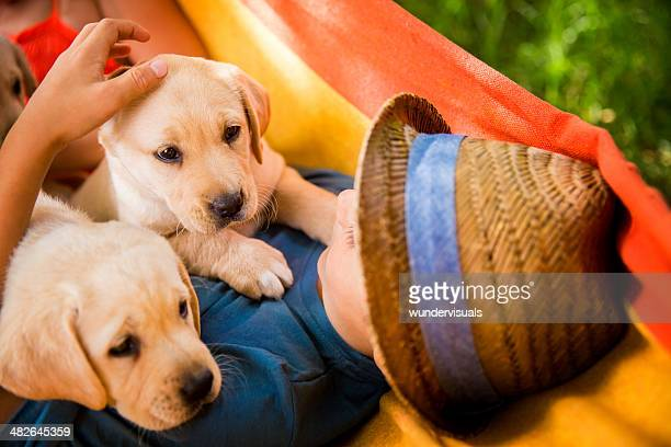 Boy lying with puppies in hammock