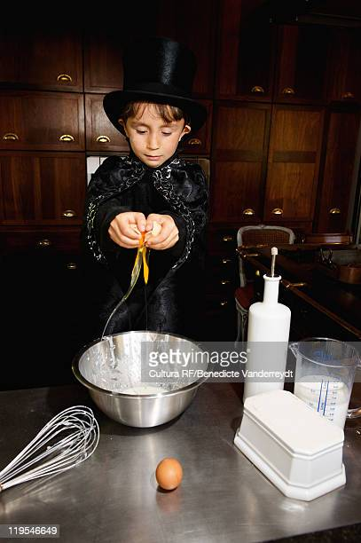 Boy magician cooking in kitchen