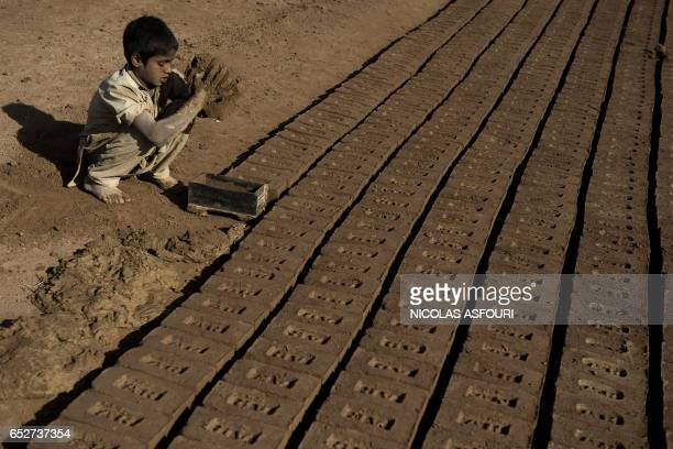 A boy makes bricks with unseen family members at a brick factory in Rawalpindi on the outskirts of capital Islamabad on November 12 2009 Families...