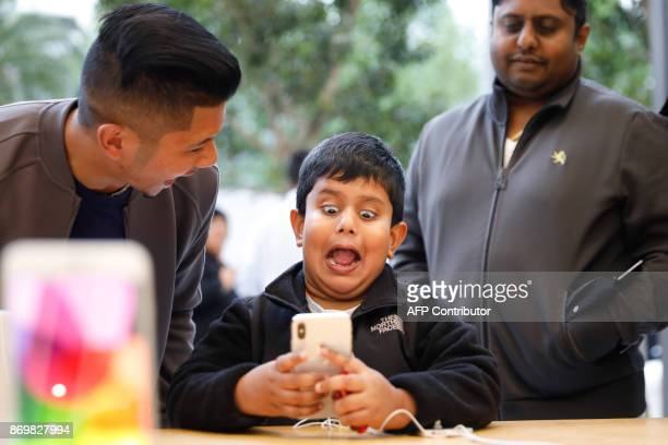 A boy makes faces while testing out the Animoji feature on an iPhone X at the Apple Store Union Square on November 3 in San Francisco California...