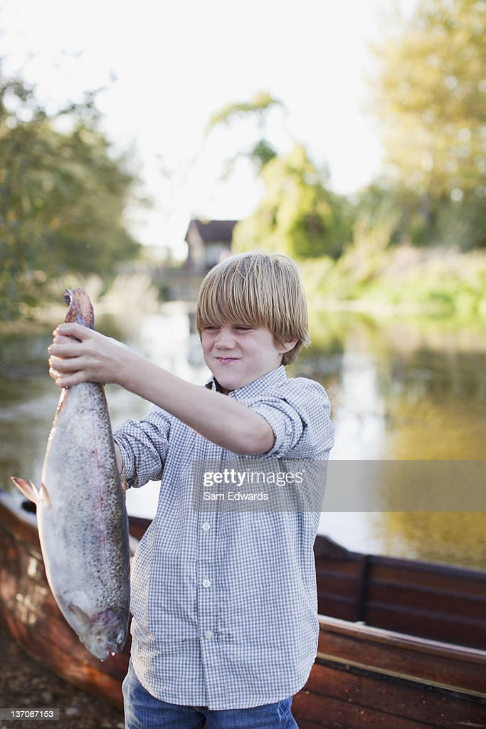 Boy making a face and holding fish in front of lake : Stock Photo