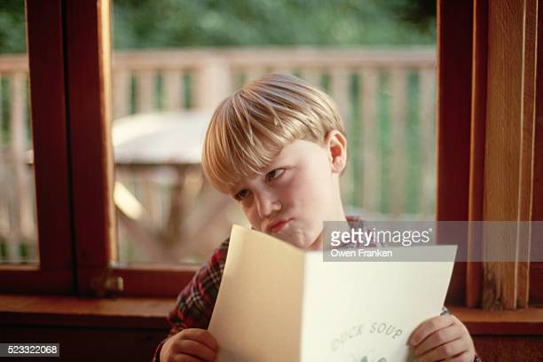 Boy Making a Face while Reading a menu