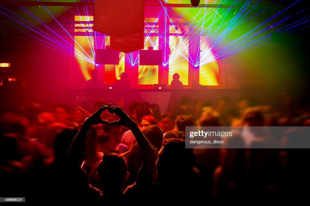 Boy making a heart shape with hands in busy club