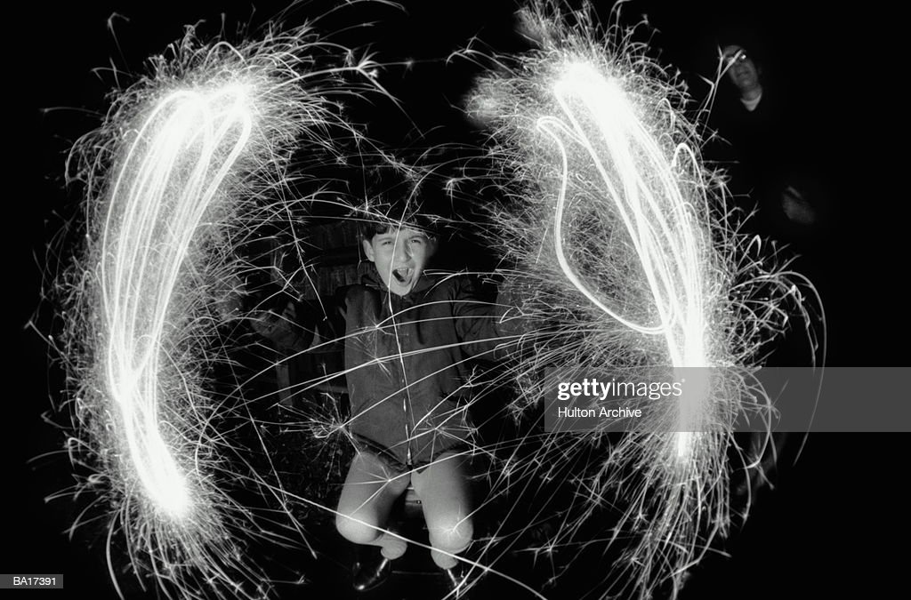 Boy (10-12) making circles with sparklers, outdoors, portrait (B&W) : Stock Photo