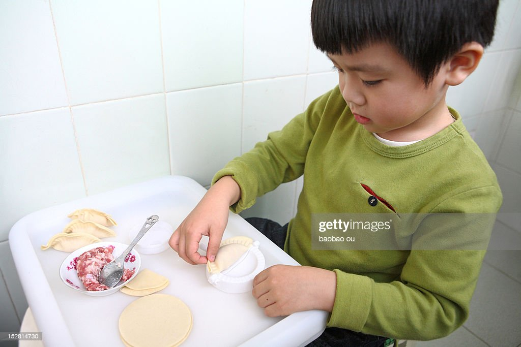 Boy making dumpling : Stock Photo