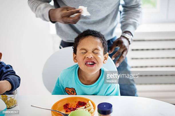 Boy making face while having food at table with father standing in background