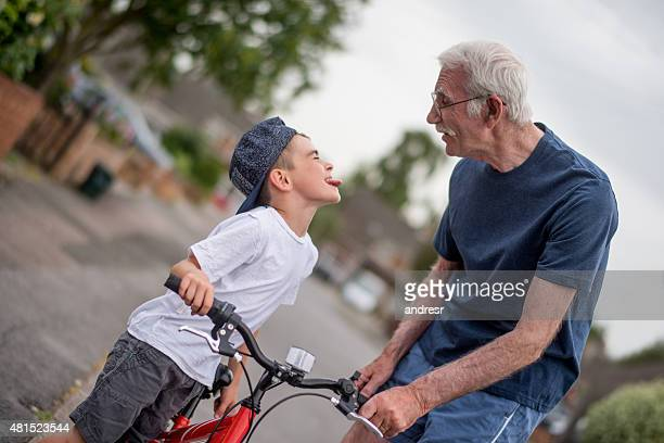 Boy making faces to his grandfather while bikw riding