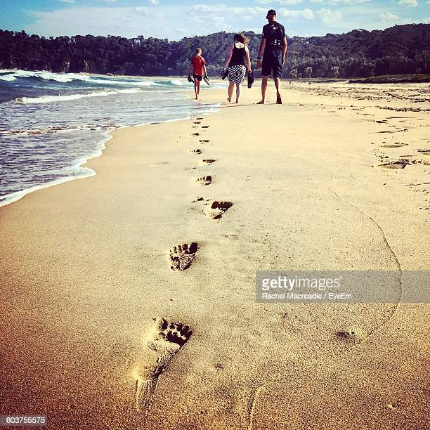 Boy Making Footprints While Walking With Parents At Beach
