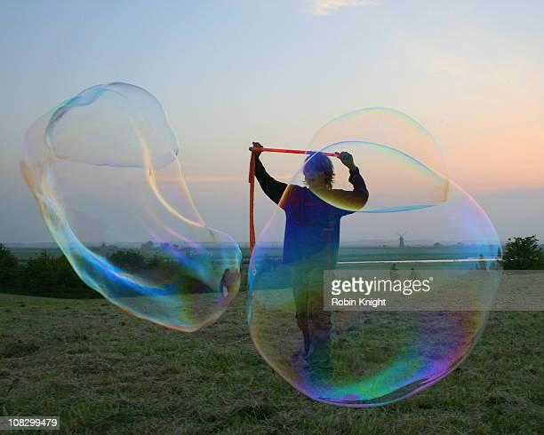 Boy making large soap bubbles