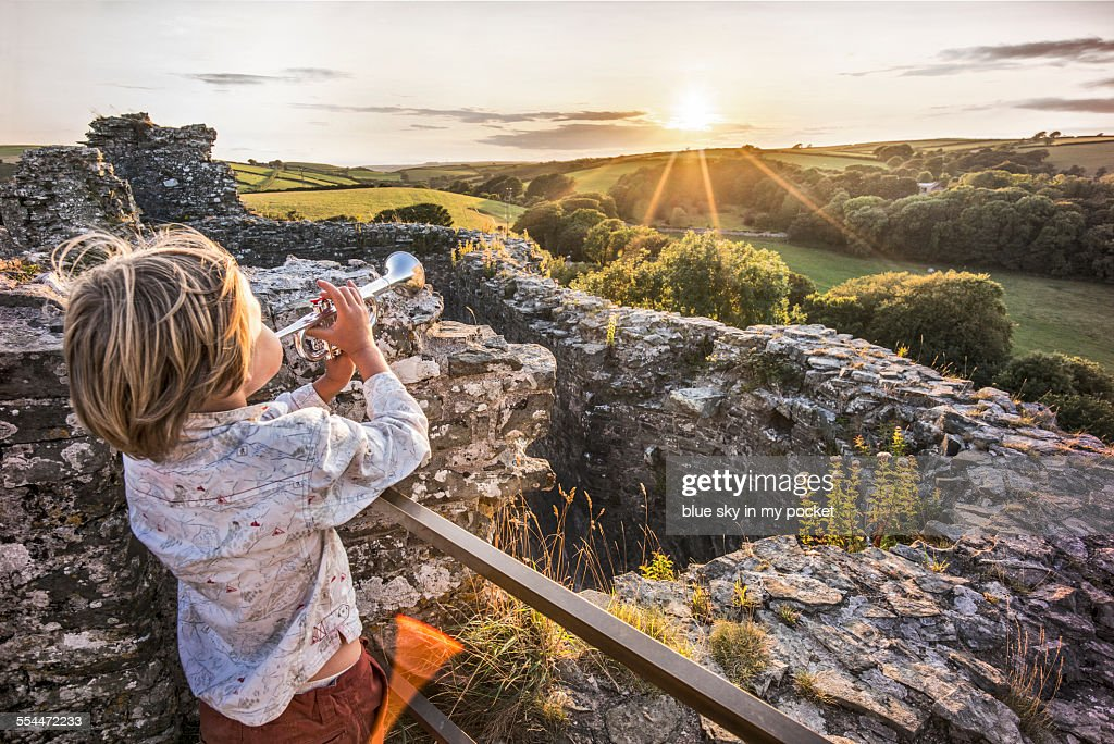 Boy making music at sunset in a Castle
