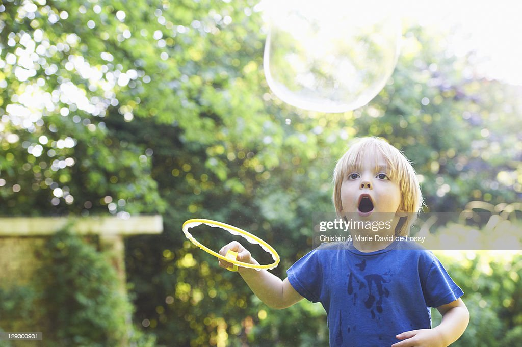 Boy making oversized bubble in backyard : Stock Photo