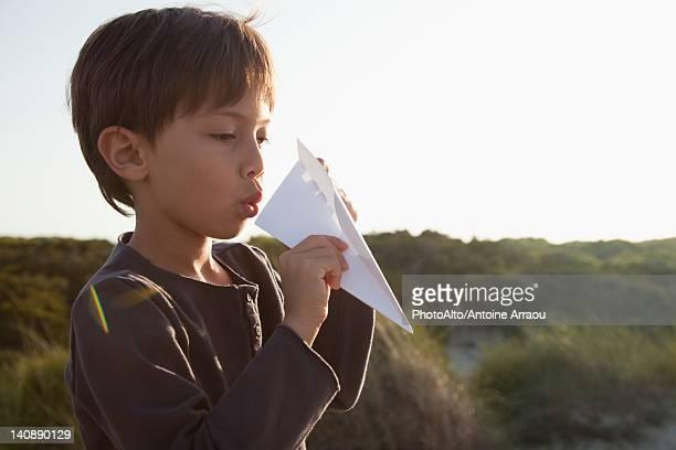 Boy making paper airplane