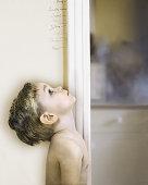 Boy (3-5) measuring self against doorway, looking up, profile