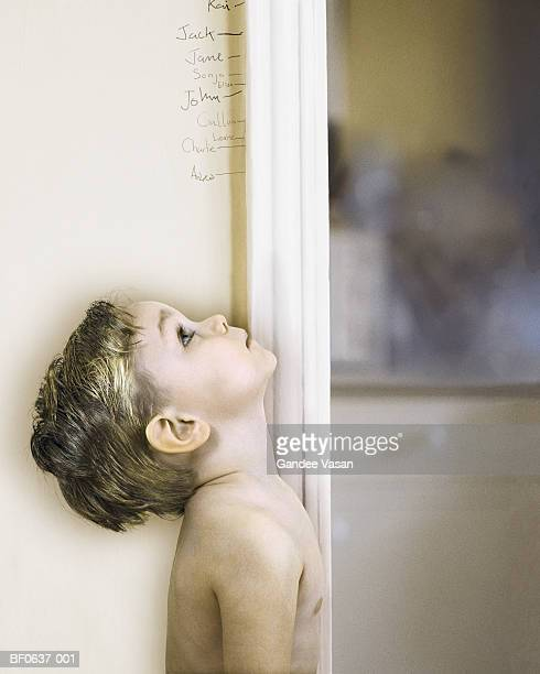Boy (3-5) measuring self against doorway, looking up, profile
