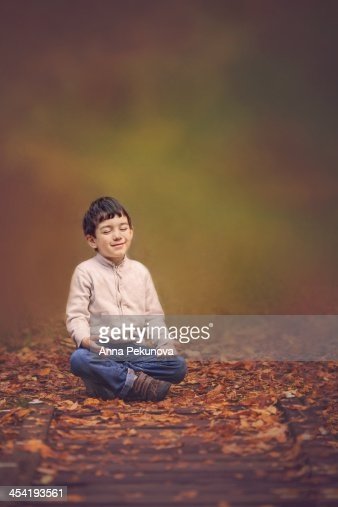 Boy meditating outdoor against blurred background : Foto de stock