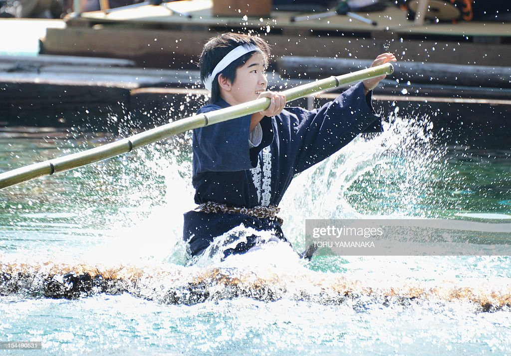 A boy, member of the Kiba 'kakunori' preservation society, falls down into the water from a floating square timber during his stunt at a local festival in Tokyo on October 21, 2012. The stunt derived from lumberjacks' daily work in the Edo period (1603-1868), when they made rafts with fire-hooks in their hands standing on floating lumbers. AFP PHOTO/Toru YAMANAKA