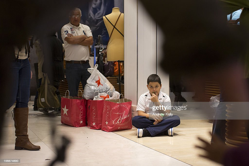 A boy minds his family's purchases in Macy's during the Black Friday sales on November 23, 2012 in New York City. Shoppers filled stores in search of the many potential bargains on offer during the traditional yearly sale, which got its name as it's said to put retailers 'in the black,' or making a profit.