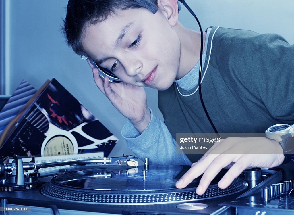 Boy (12-14) mixing record on turntable, close-up : Stock Photo