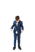 Adorable stylish handsome boy posing in modern kids suit and showing to his shoes, Ugly shoes do not match with the suit, Isolated on white background