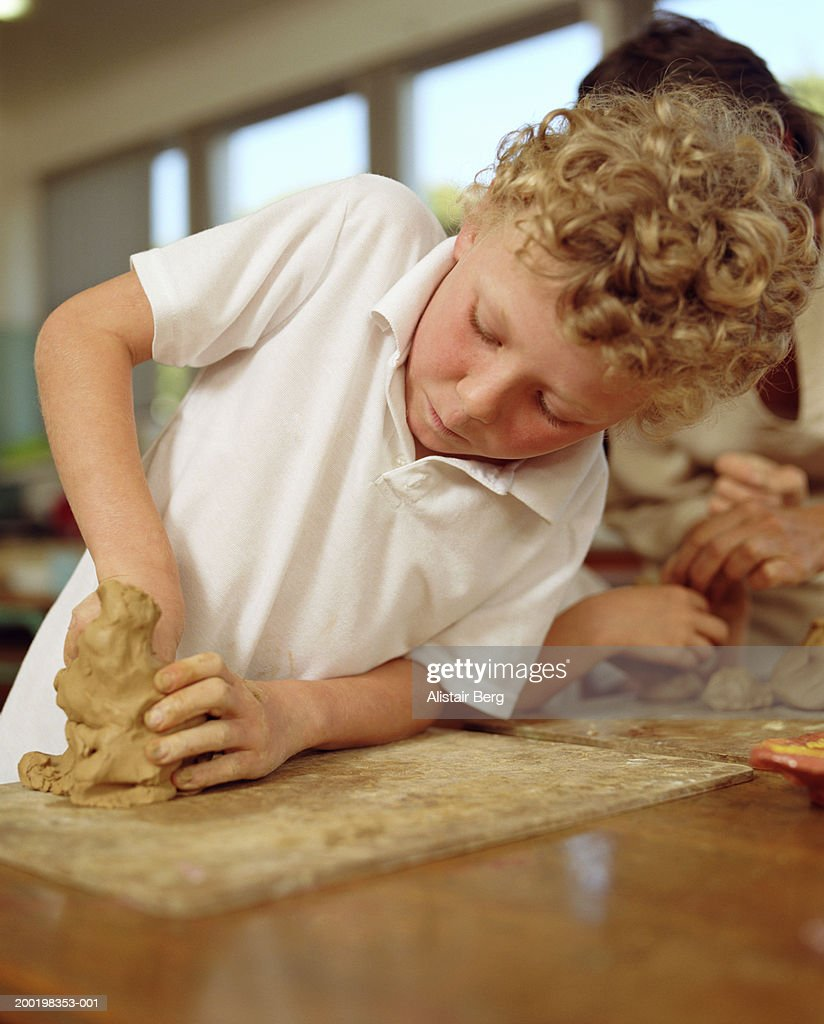 Boy (6-8) modelling clay in classroom : Stock Photo