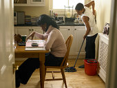 Boy (12-13) mopping kitchen floor behind mother counting bills