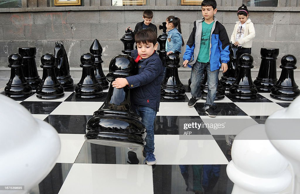 A boy moves a pawn as he plays giant chess in central Yerevan on April 26, 2013. AFP PHOTO / KAREN MINASYAN