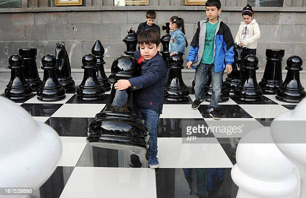 A boy moves a pawn as he plays giant chess in central Yerevan on April 26 2013 AFP PHOTO / KAREN MINASYAN