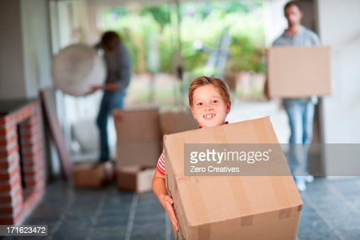 Boy moving house carrying cardboard box : Stock Photo