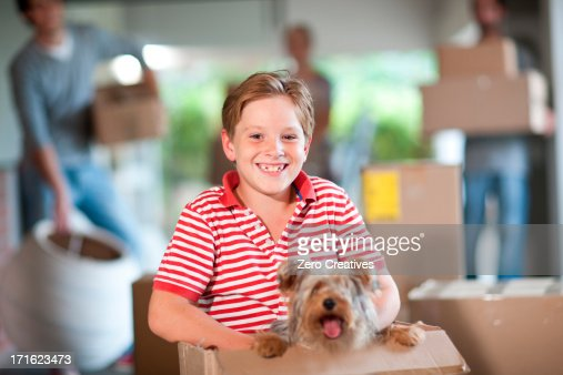 Boy moving house with dog in box : Stock Photo