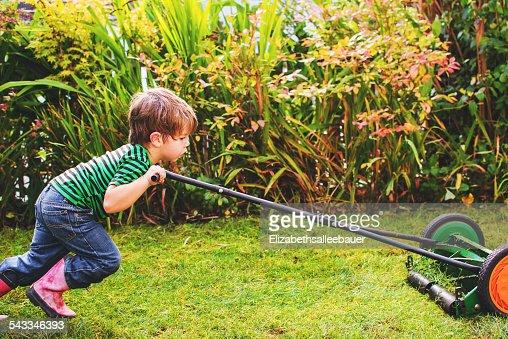 Boy (2-3) mowing lawn