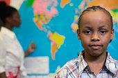 Boy near map in classroom