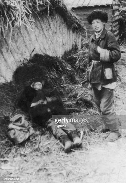 A boy next to the body of his father after the man was shot for approaching a prohibited area of a farm while picking grain during the manmade...