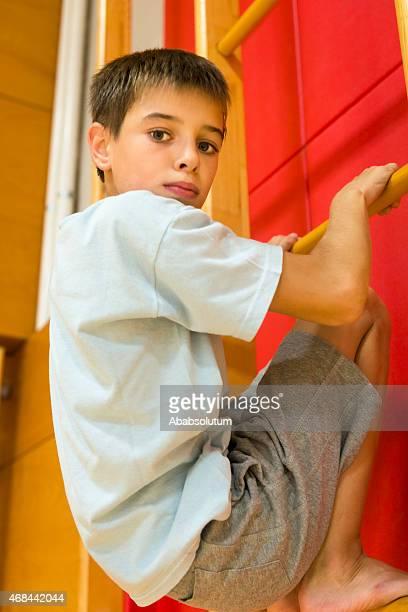 Garçon de onze gymnastique d'escalade échelle au gymnase, l'Europe