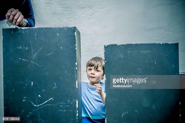 Boy of Four Among Black Boxes, Father Beside, Paris, France