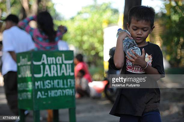 A boy offers water in a bottle for hand washing as Muslims make pilgrimages to the graves of family members during Ramadan on June 17 2015 in...