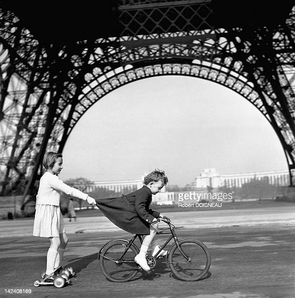 A boy on a bicycle is towing a girl with roller skate under the Eiffel Tower on Le Champs de Mars, Paris, France in 1943.