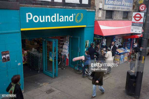 A boy on a bike holds an inflatable penis outside a Poundland on the Walworth Road on 31st March 2017 in south London England