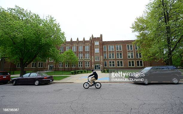 A boy on a bike passes the Wilbur Wright Elementary School May 8 2013 in Cleveland Ohio where Gina DeJesus attended classes a decade ago before she...
