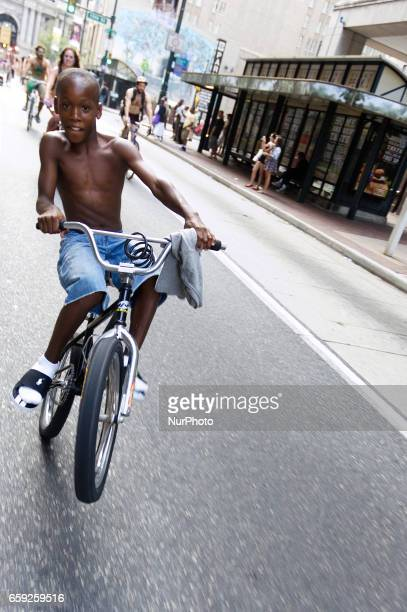 Boy on a bike pulls a Wheelie as he rides in front of a group of cyclist participating in the Sept 4 2011 Philly Naked Bike Ride on Market Street in...