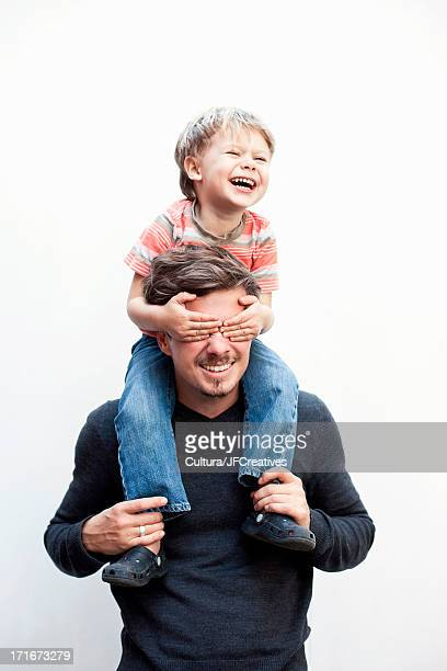 Boy on a father's shoulders, covering his eyes