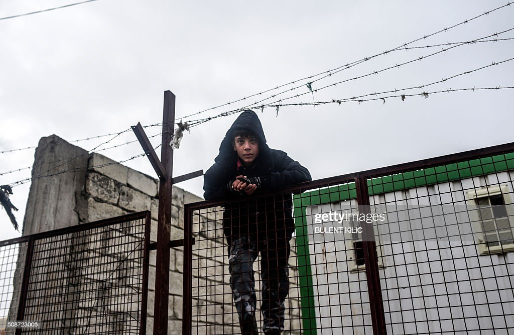 A boy on a fence looks on as Syrians fleeing the northern embattled city of Aleppo wait on February 6, 2016 in Bab-Al Salam, near the city of Azaz, northern Syria, near the Turkish border crossing. Thousands of Syrians were braving cold and rain at the Turkish border Saturday after fleeing a Russian-backed regime offensive on Aleppo that threatens a fresh humanitarian disaster in the country's second city. Around 40,000 civilians have fled their homes over the regime offensive, according to the Syrian Observatory for Human Rights monitor. / AFP / BULENT KILIC