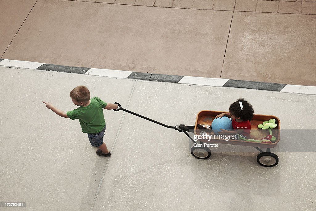 Boy Pulling Wagon : Boy on a journey pulling girl in red wagon stock photo