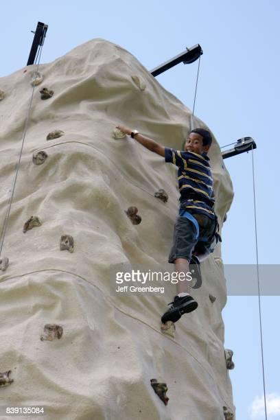 A boy on a rock climbing simulator at Tropical Park
