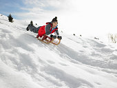 Pre-teen Boy On A Sled Playing In The Snow