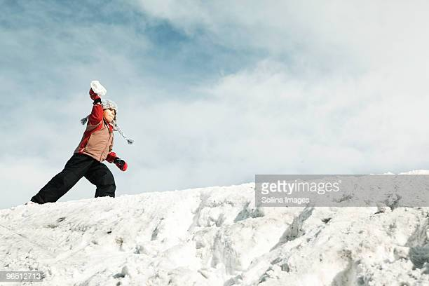 Boy on a snow ridge throwing a snowball
