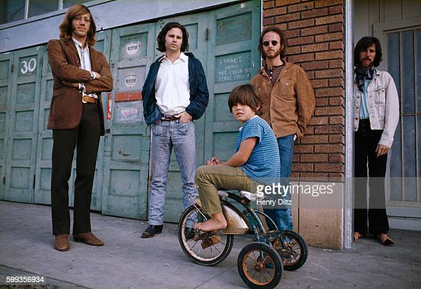 A boy on a tricycle sits among the rock band the Doors who are keyboardist Ray Manzarek singer Jim Morrison guitarist Robbie Krieger and drummer John...